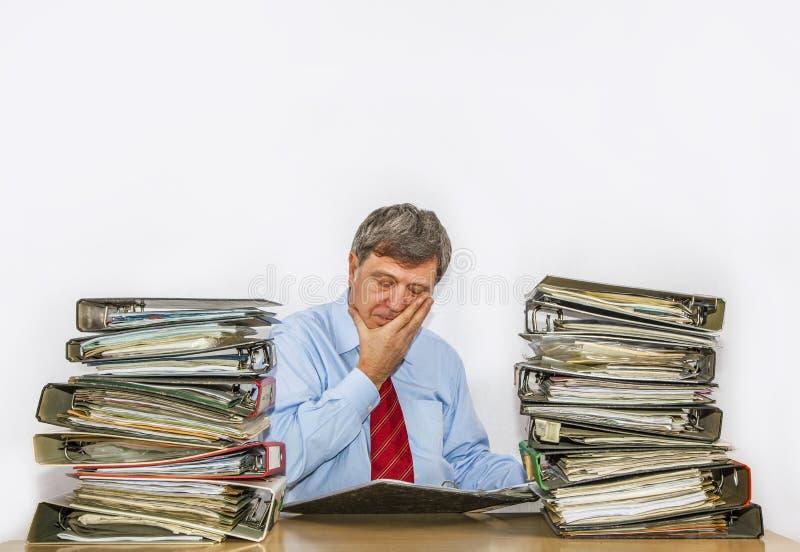 De mens bestudeert omslag met dossiers bij zijn bureau stock afbeeldingen