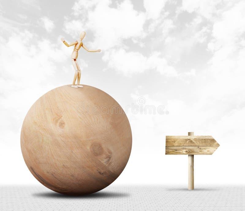De mens bevindt zich op de bovenkant van een reusachtige houten bal en het op weg zijn naar de wijzer stock afbeelding