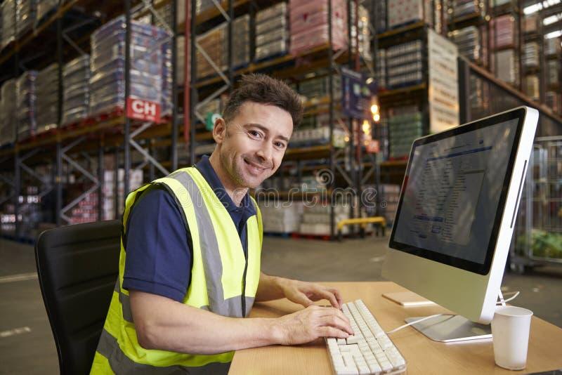 De mens bij computer in pakhuisbureau ter plaatse kijkt aan camera stock foto's