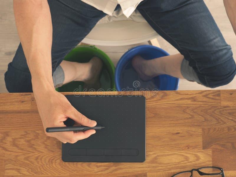De mens bij het bureau koelt zijn voeten royalty-vrije stock afbeelding