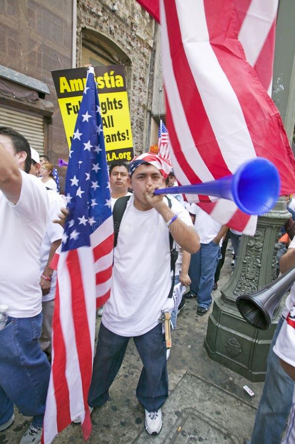 De mens blaast hoorn met honderdduizenden immigranten die aan maart voor Immigranten en Mexicanen deelnemen die tegen Ille protes stock foto's