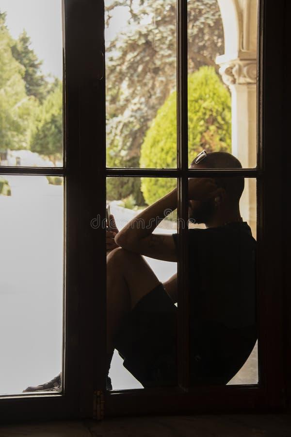 De mens in borrels en de zitting van het T-stukoverhemd in venster die cel bekijken telefoneren onherkenbaar bijna silhouet stock afbeeldingen