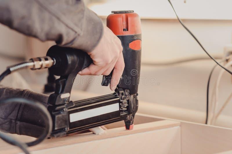 De mens bouwt meubilair in de timmerwerkwinkel stock fotografie