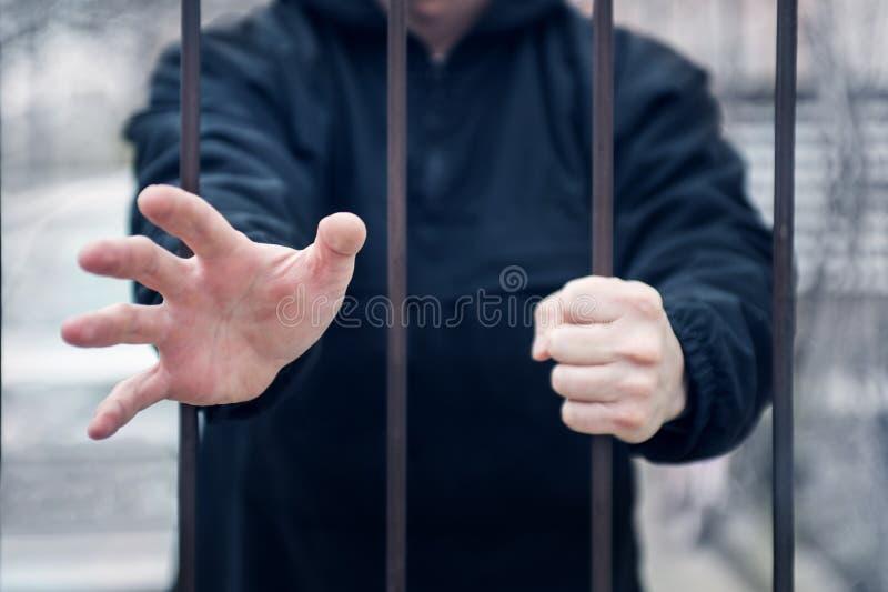 De mens breidt zijn hand voor hulp van kooi uit Close-up op handen van mensenzitting in gevangenis, gevangeneconcept Hoop vrij te royalty-vrije stock foto