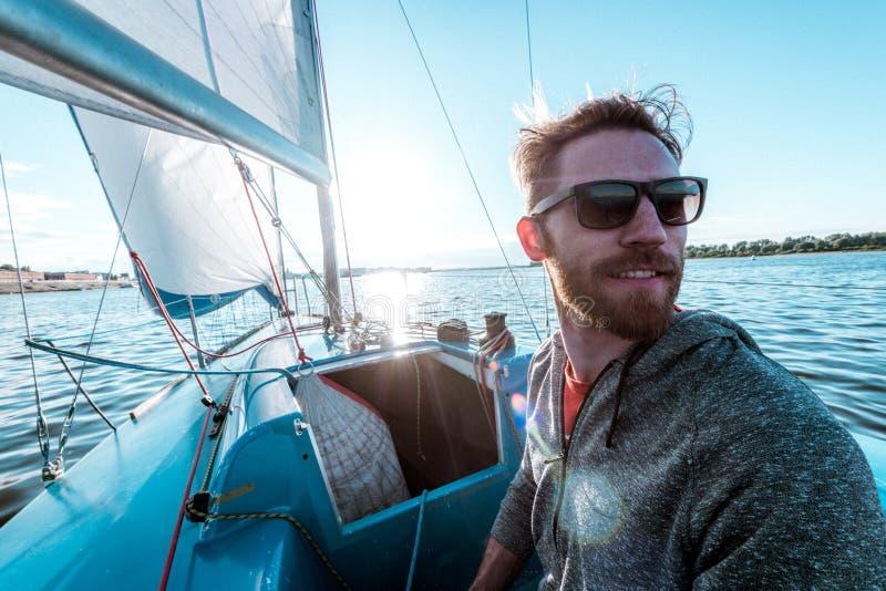 De mens controleert boot gebruikend uitloper bij achtersteven tijdens het varen op rivier bij de zomerdag stock foto
