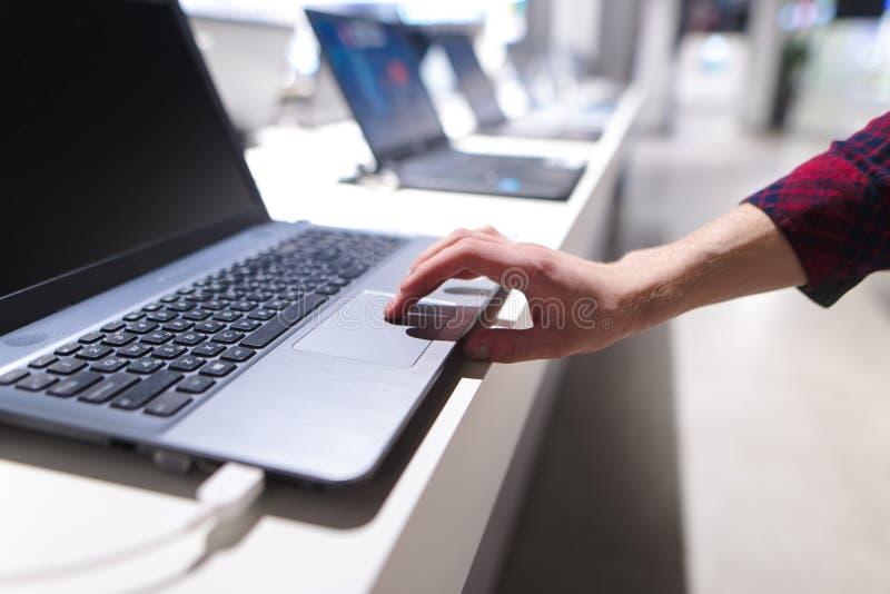de mens controleert de computer met een touchpad Een man hand gebruikt laptop in de elektronikaopslag stock fotografie