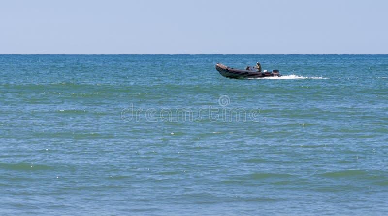 De mens controleert een krachtige motorboot stock afbeeldingen