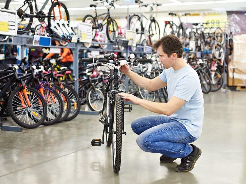 De mens controleert fiets alvorens sporten in te kopen winkel royalty-vrije stock afbeeldingen