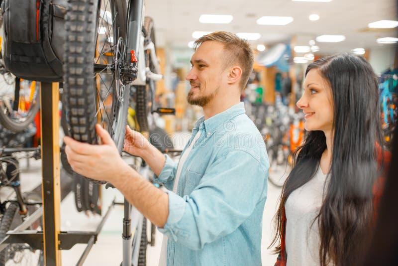 De mens controleert de onderbrekingen van de fietsschijf, het winkelen stock afbeelding