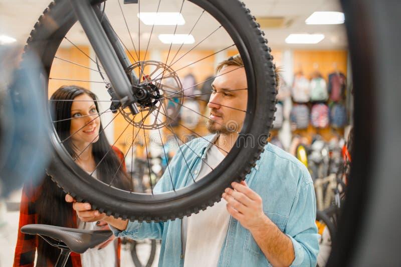 De mens controleert de onderbrekingen van de fietsschijf, het winkelen stock fotografie