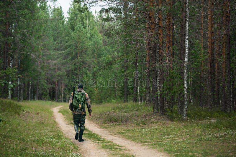 De mens de jager gaat op een bosweg stock fotografie