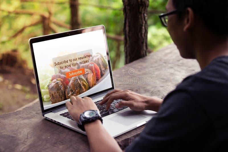 De mens die aan laptop/computer, het doen werken tekent voedselblog op het scherm in stock afbeelding