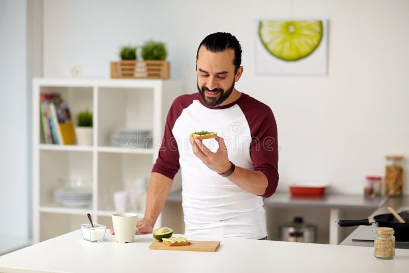 De mens die avocado eten klemt thuis keuken stock afbeelding