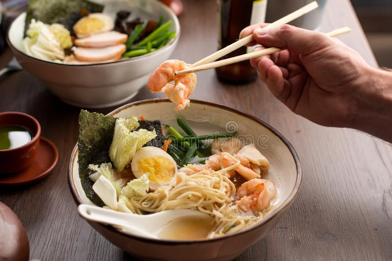 De mens die Aziaat eten ramen met garnalen en noedels in een restaurant stock foto