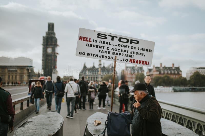 De mens die een bericht in een raad met betrekking tot Jesus, in het midden van de Brug van Westminster, met toeristen rond hem t stock fotografie