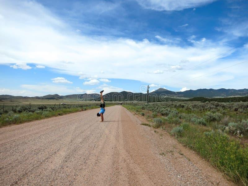 De mens die een hoed, een t-shirt, borrels, en pantoffels dragen doet Handstanden stock afbeelding