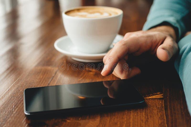 De mens die een smartphone gebruiken en drinkt koffieachtergrond royalty-vrije stock afbeeldingen
