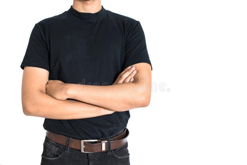 De mens die en doet wapenskruisen op ge?soleerde witte achtergrond bevinden zich Zwarte T-shirt en jeans met bruine riem in Manie stock afbeelding