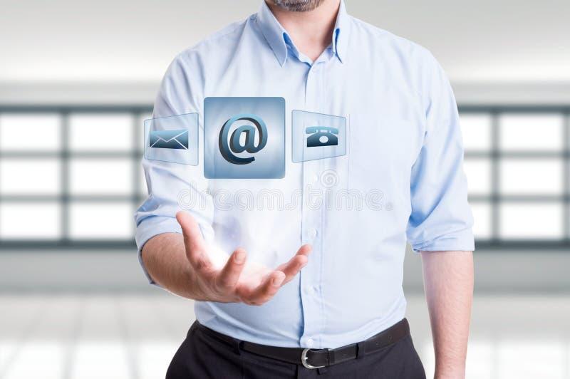 De mens die futuristisch contacteert ons drijvende pictogrammen houden stock afbeelding