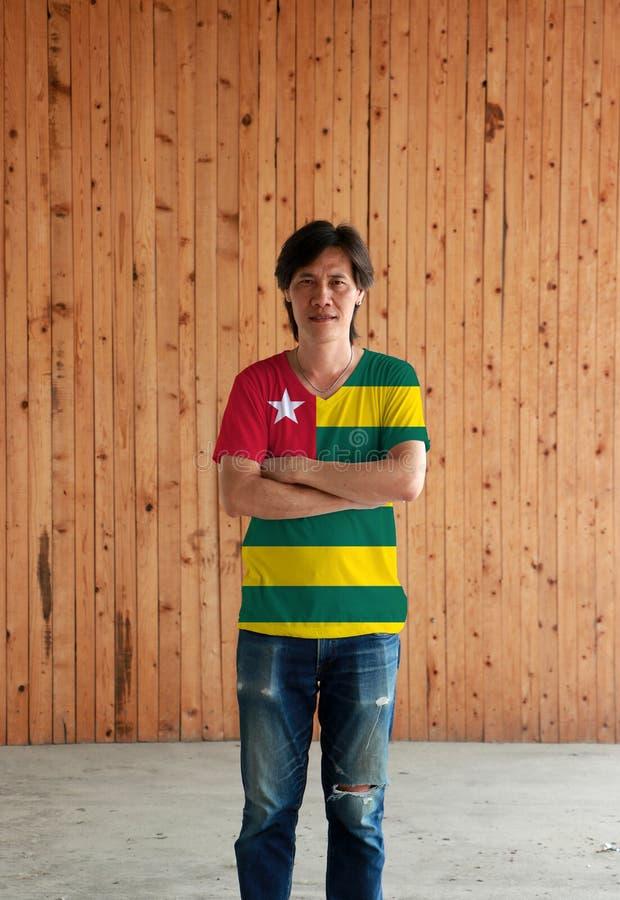 De mens die het overhemd van de de vlagkleur van Togo dragen en kruist zijn wapen op houten muurachtergrond royalty-vrije stock foto's