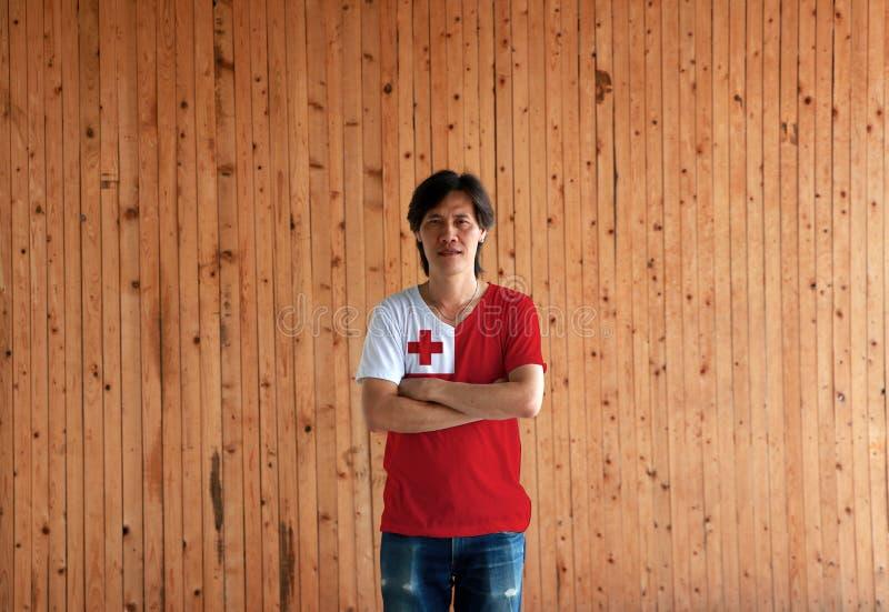 De mens die het overhemd van de de vlagkleur van Tonga dragen en kruist zijn wapen op houten muurachtergrond stock foto's