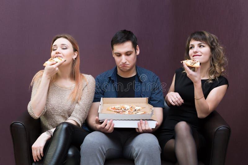 De mens die kijkt als meisjes eet pizza op dieet zijn stock afbeelding