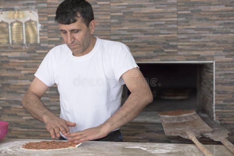De mens die Lahmacun-Deeg voorbereiden met hakt Vlees op het Keukenbureau Turkije fijn 30 Augustus 2015 stock foto