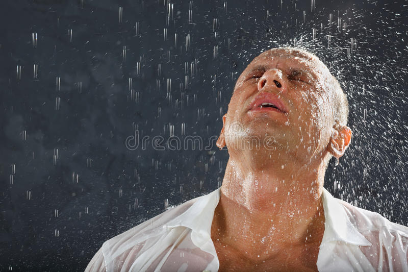 De mens die nat overhemd draagt bevindt zich in regen stock foto