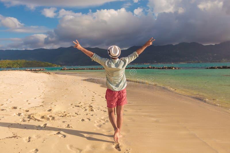 De mens die op het strand lopen en viert zijn joyous leven royalty-vrije stock fotografie