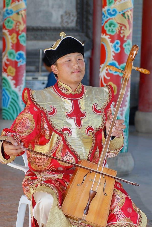De mens die traditioneel kostuum dragen voert muziek met morin uit khuur - nationaal muzikaal instrument in Ulaanbaatar, Mongolië royalty-vrije stock foto's