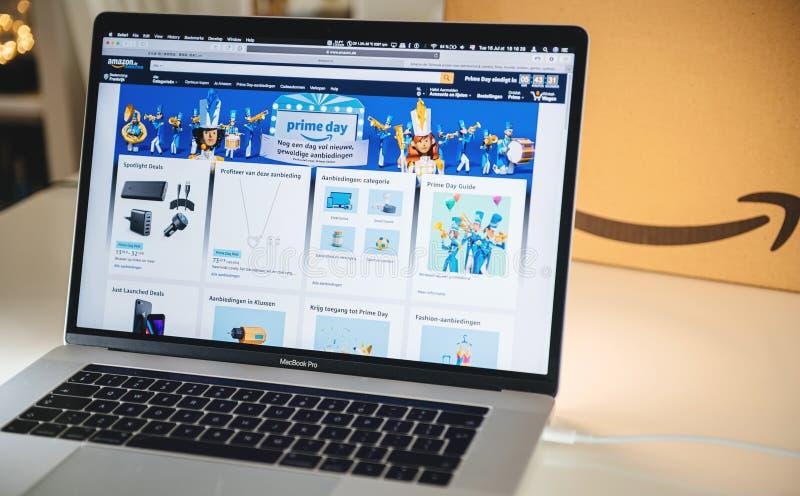 De mens die van de Amazon Primedag op laptop overeenkomsten winkelen stock afbeeldingen