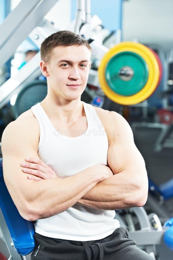 De mens die van de bodybuilder de oefeningen van de bicepsenspier doet stock fotografie