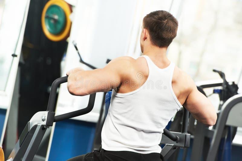 De mens die van de bodybuilder oefeningen in geschiktheidsclub doen royalty-vrije stock foto's