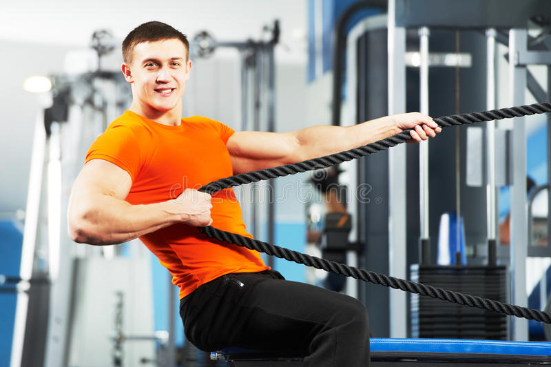 De mens die van de bodybuilder oefeningen in geschiktheidsclub doen royalty-vrije stock fotografie