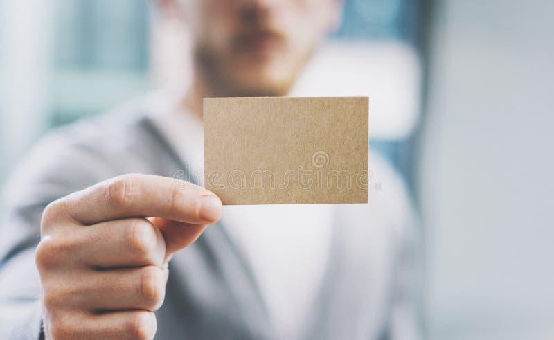 De mens die van de close-upfoto toevallig overhemd dragen en leeg ambachtadreskaartje tonen Vage achtergrond Klaar voor privé royalty-vrije stock fotografie