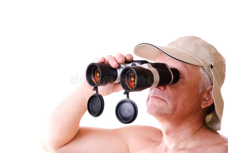 De mens die van de safari door zijn binoculair kijkt royalty-vrije stock foto