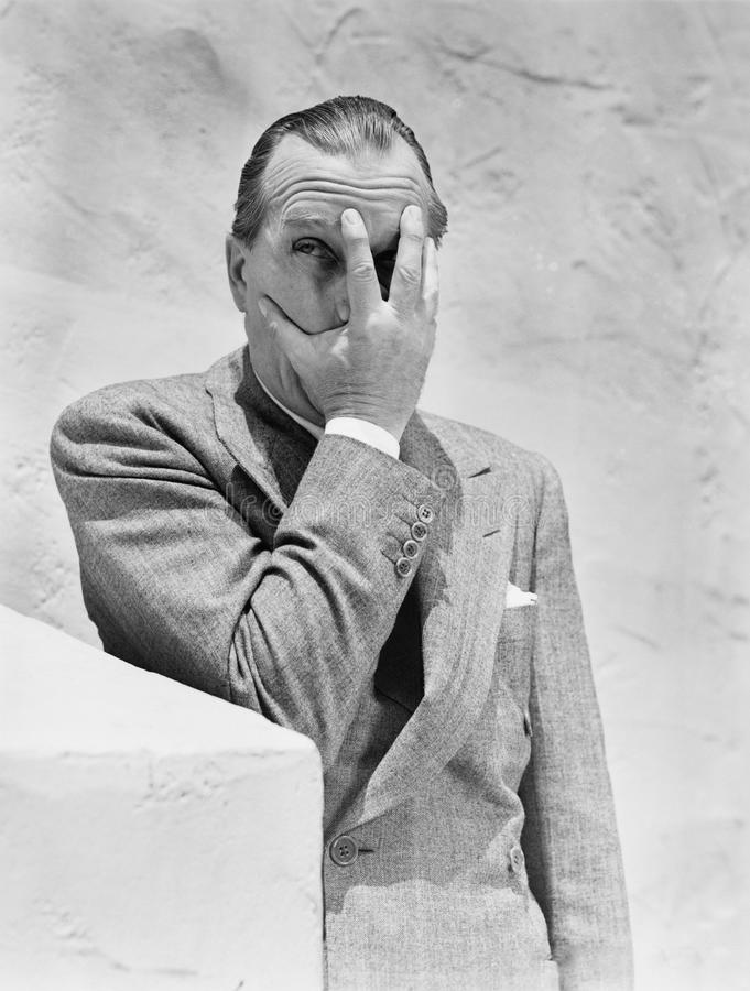 De mens die van hem zetten dient voorzijde van zijn gezicht en het gluren door zijn vingers in (Alle afgeschilderde personen leve stock foto