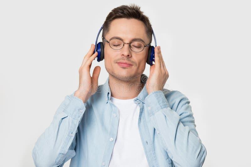 De mens die van het Headshotportret hoofdtelefoons gesloten ogen dragen geniet van favoriete muziek royalty-vrije stock afbeeldingen