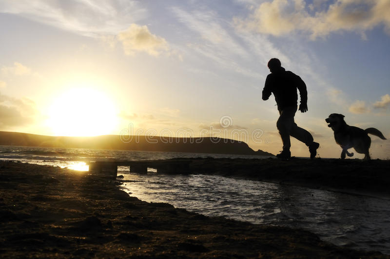 De Mens die van het silhouet met Hond loopt. stock foto's