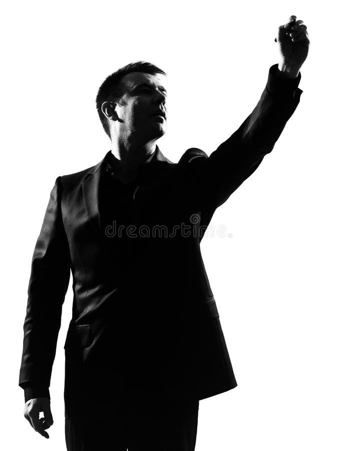 De mens die van het silhouet op exemplaarruimte schrijft stock fotografie