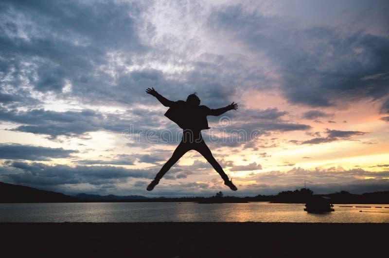 De mens die van het silhouetgeluk op meer bij zonsondergang springen royalty-vrije stock afbeeldingen