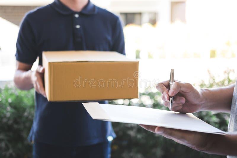 De mens die van de leveringspost pakketdoos geven aan de begunstigde, Jonge mens die ontvangstbewijs van leveringspakket thuis on royalty-vrije stock afbeelding