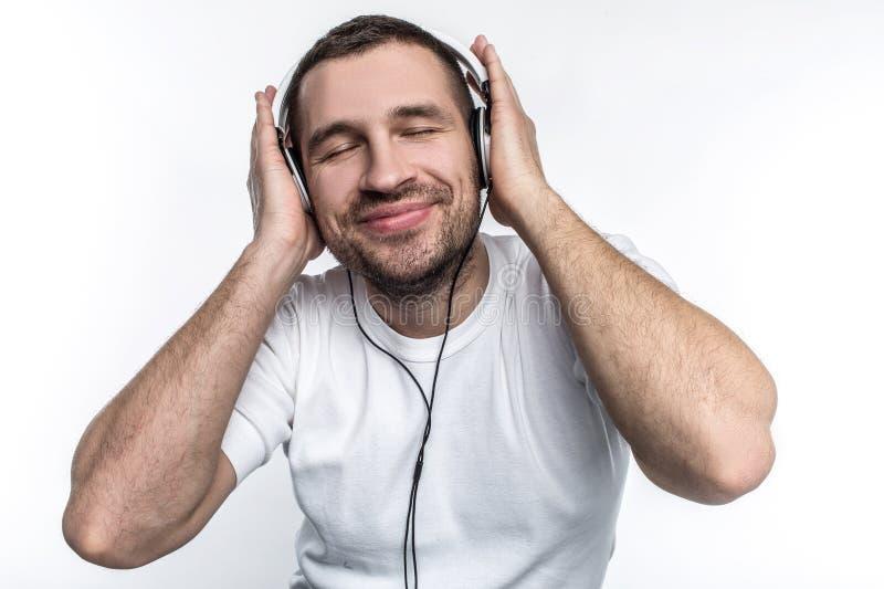 De mens die van Nice aan muziek luisteren en van het ogenblik genieten Hij houdt van verschillend te luisteren soort muziek Geïso stock afbeeldingen