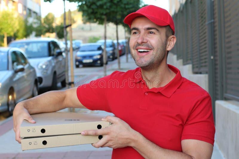 De mens die van de pizzalevering camera bekijken stock foto's