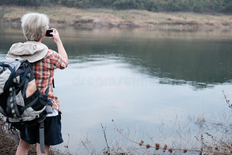 De mens die van de reizigerswandelaar met rugzak dichtbij meer wandelen toerist backp stock foto's