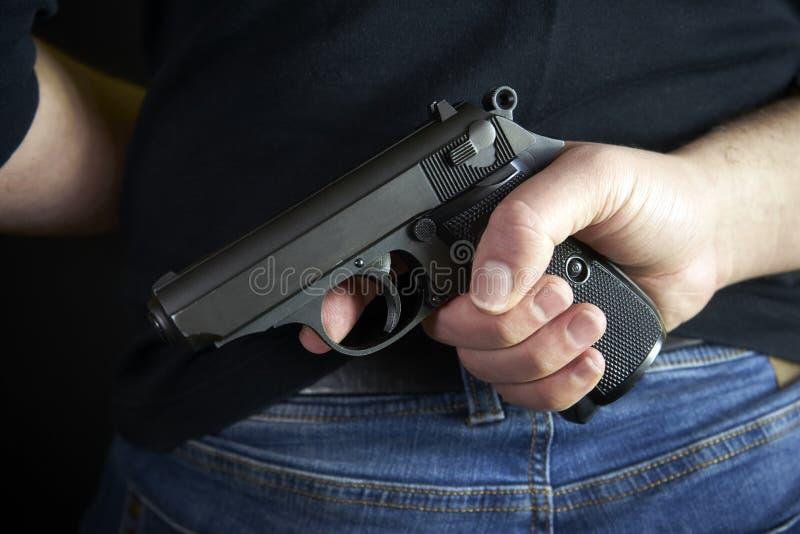 De mens die van de terroristendief kort kanon in zijn hand houden Verborgen kanon op achterkantlichaam stock afbeeldingen
