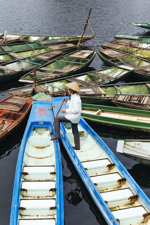 De mens die wit overhemd dragen, kegelhoed met zijn peddeltribune op blauwe lege boot met vele boten houdt over de rivier op stock foto's