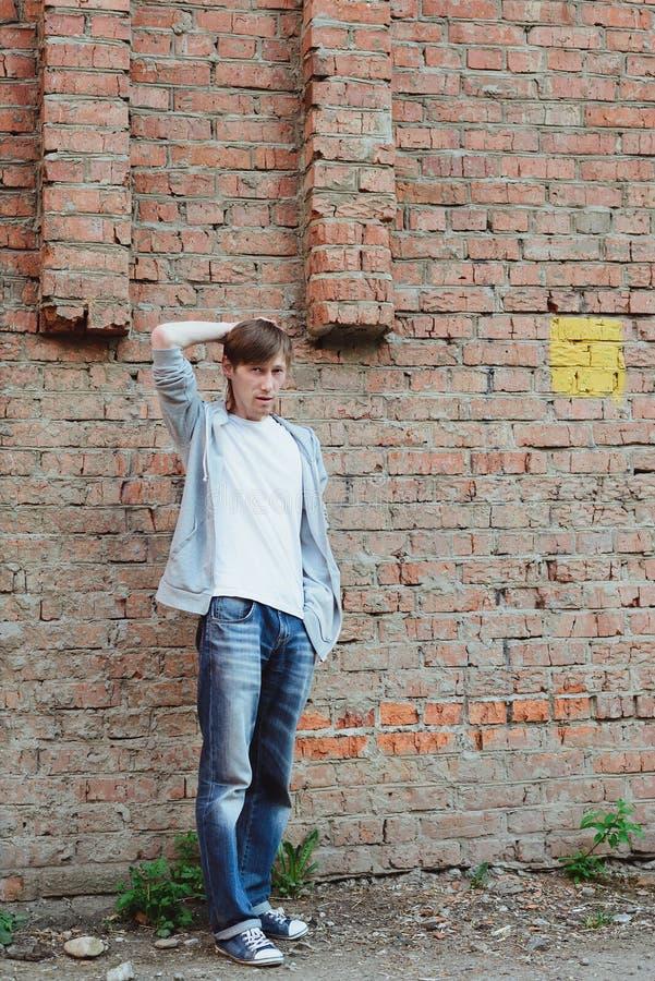 De mens die zich in volledige grootte dichtbij bakstenen muur achtergrond en het krassen rechten bevinden overhandigt uw hoofdenh royalty-vrije stock fotografie