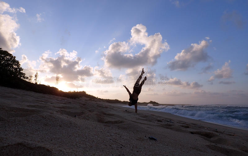 De mens doet één handhandstand op strand bij zonsondergang stock foto's