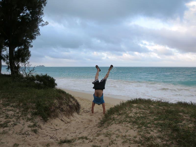 De mens doet handstand in het zand die t-shirt en borrels op dragen stock fotografie